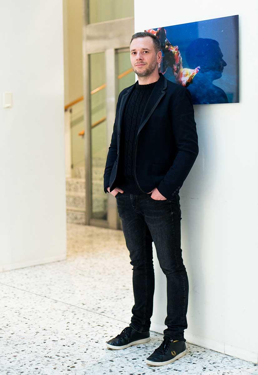 MArko Zink, schwarz gekleidet vor blauem Bild