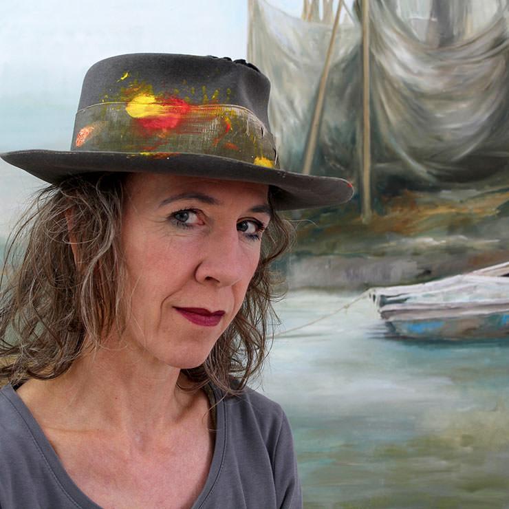 Maria Temnitschka Portrait mit bemalten Hut vor einem BIld mit Meer und Boot