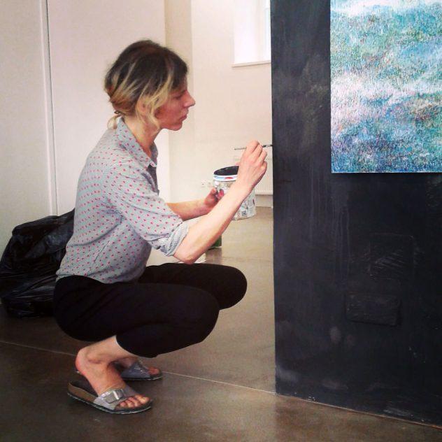 Linda Berger in Seitenansicht, hockend mit Pinsel in der Hand, konzentriert an einer Wand malend.