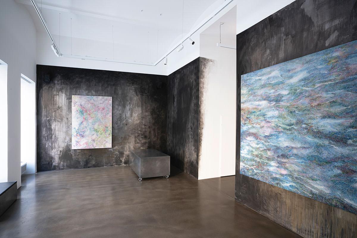 Raumansicht Bildraum07. Schwarz bemalte Wände mit großsflächigen Bunten Bildern, die aus kleinen Strichen zusammengesetzt sind.