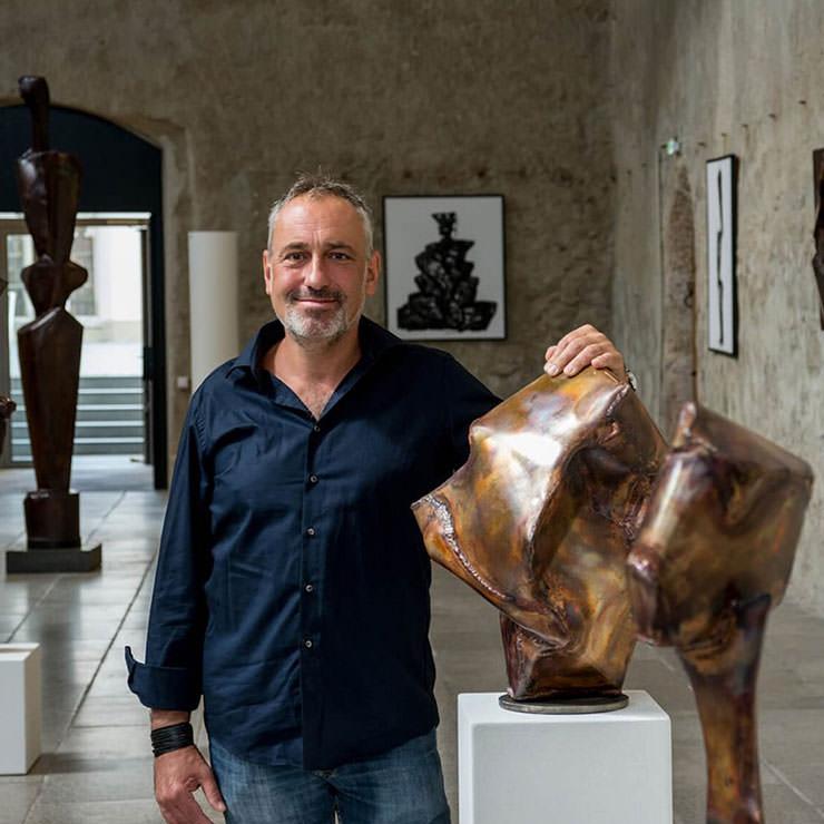 Künstler mit Hand auf seiner Bronzeskulptur