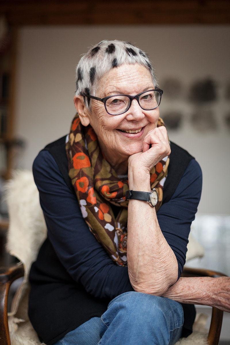 Frau lachend sitzend mit aufgestütztem Unterarm und kurzen weissen Haaren mit schwarzen Flecken