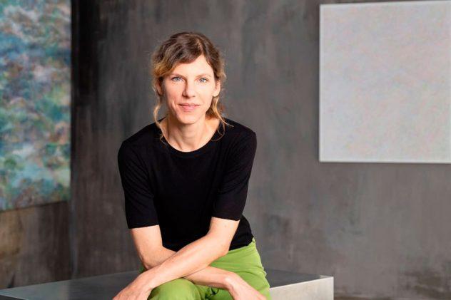 Porträtfoto einer sitzenden Frau mit lässig überkreuzten Armen