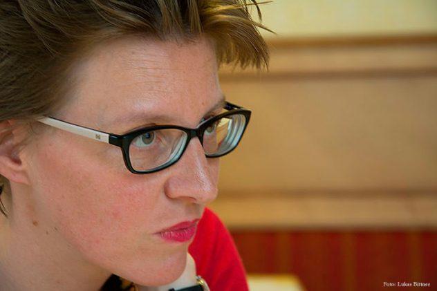 Nahes Gesichtsporträt von einer Frau mit Brille und konzentriertem Ausdruck