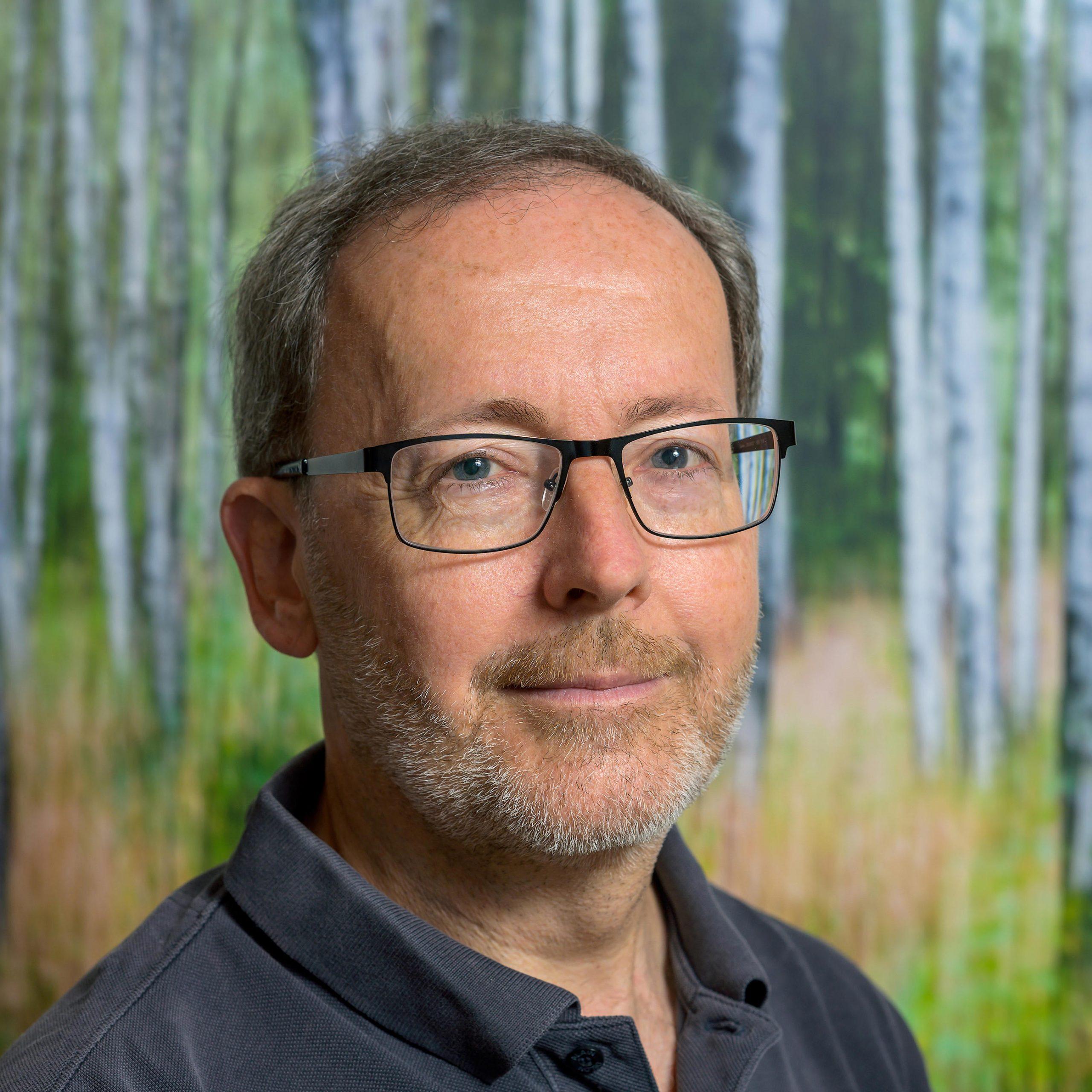 Kopfportrait eines Mannes vor einem Bild mit Baumstämmen