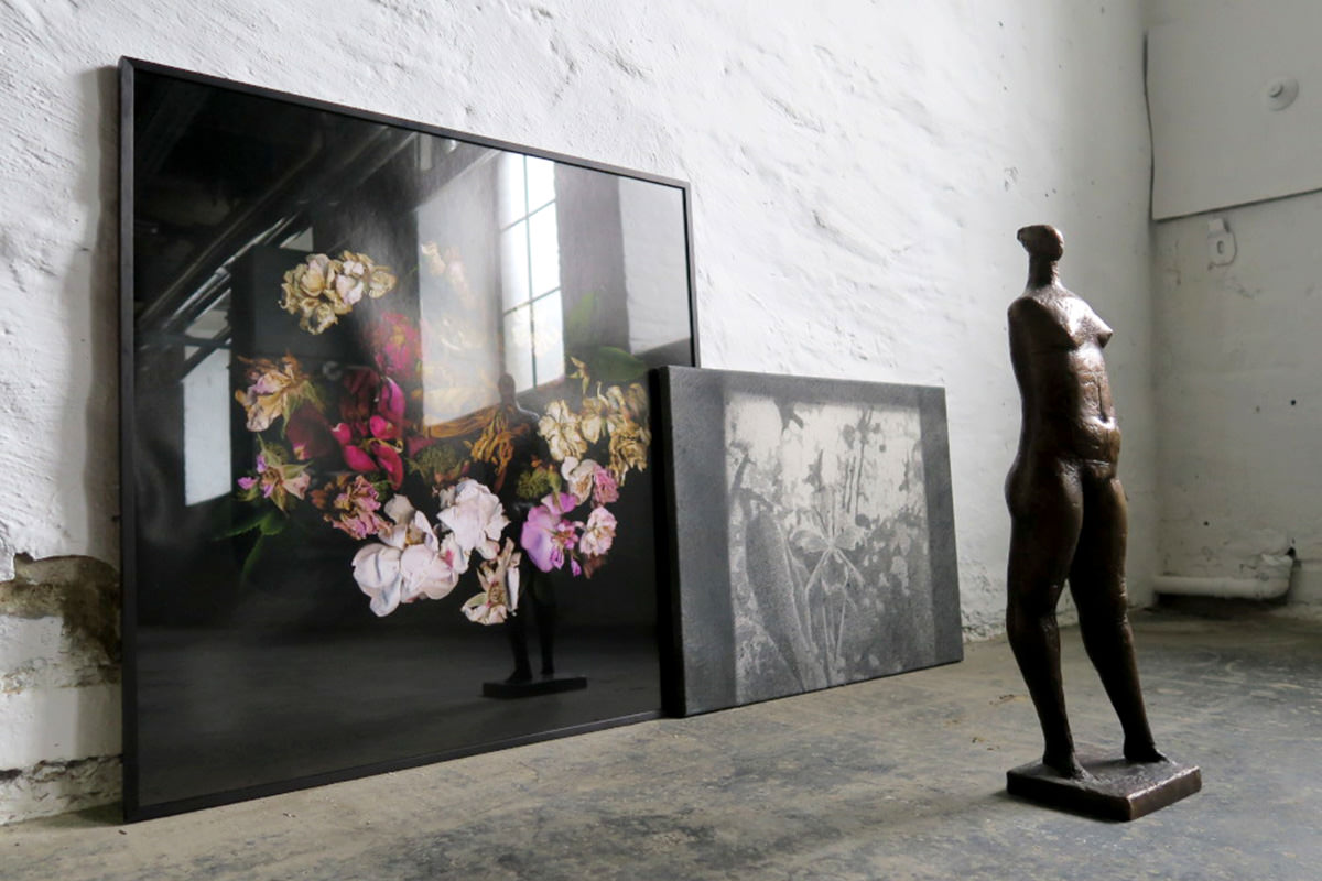 Dunkler Raum mit Bildern an der Wand lehnend und einer menschlichen Skulptur