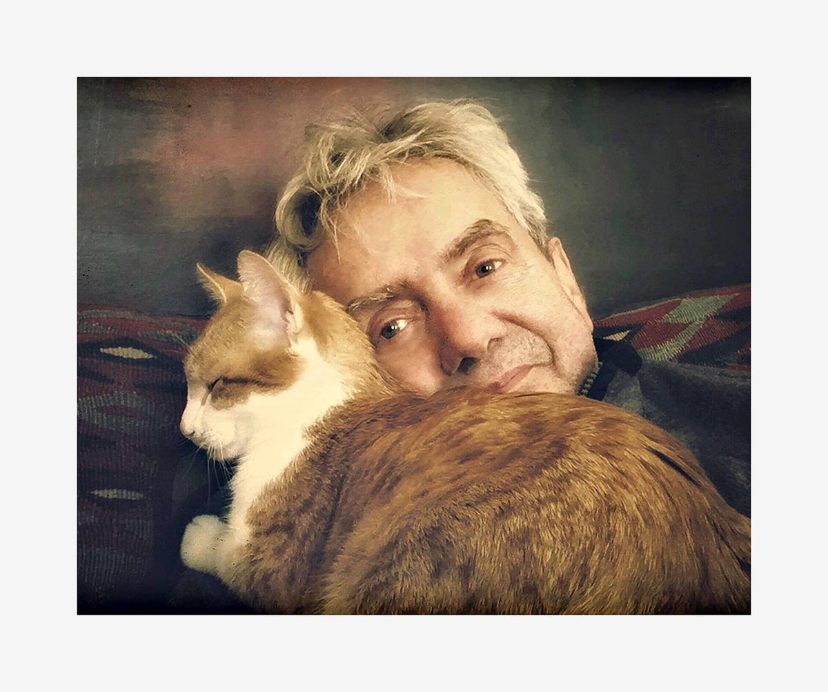 Portrait eines Mannes mit blondesn Haaren und einer rotgoldenen Katze